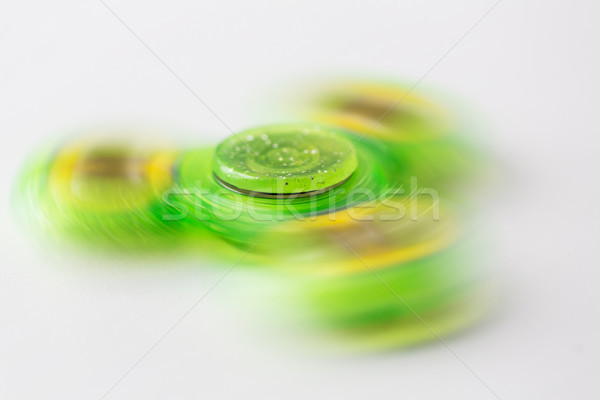 Stock photo: close up of lime green spinning fidget spinner