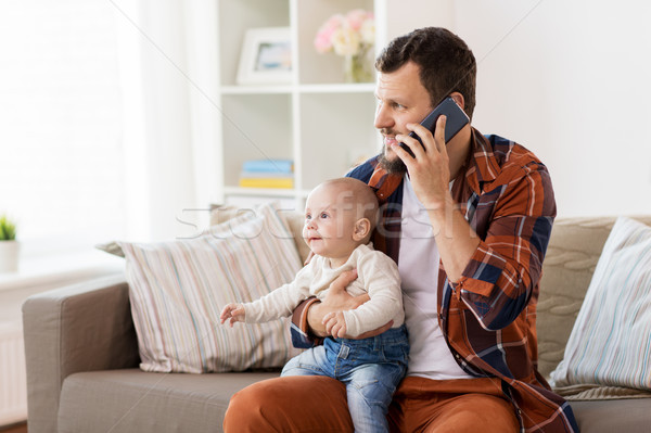 father with baby calling on smartphone at home Stock photo © dolgachov
