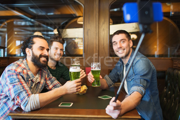 friends taking selfie and drinking beer at bar Stock photo © dolgachov