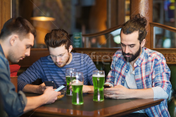 friends with smartphones and green beer at pub Stock photo © dolgachov