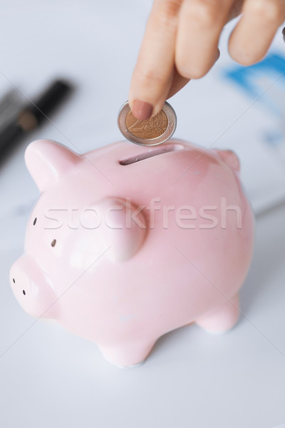 woman hand putting coin into small piggy ban Stock photo © dolgachov