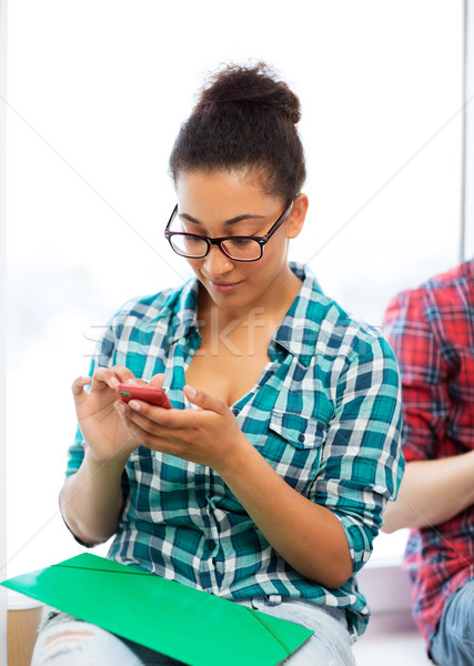 african student browsing in smartphone at school Stock photo © dolgachov