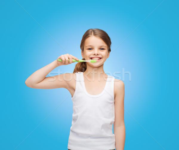 Stock photo: girl in blank white shirt brushing her teeth