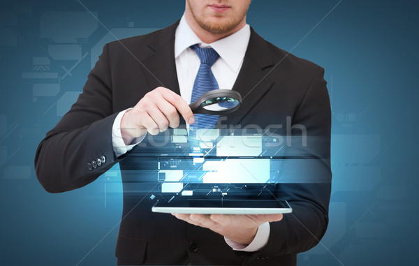 businessman hand holding magnifier over tablet pc Stock photo © dolgachov