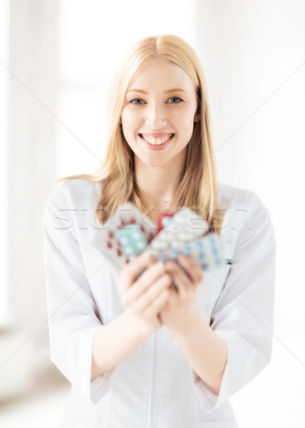 young female doctor with pack of pills Stock photo © dolgachov