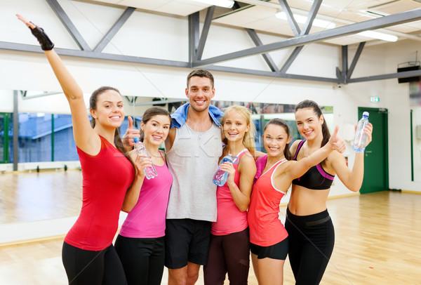 Grupo pessoas felizes água garrafas toalha fitness Foto stock © dolgachov