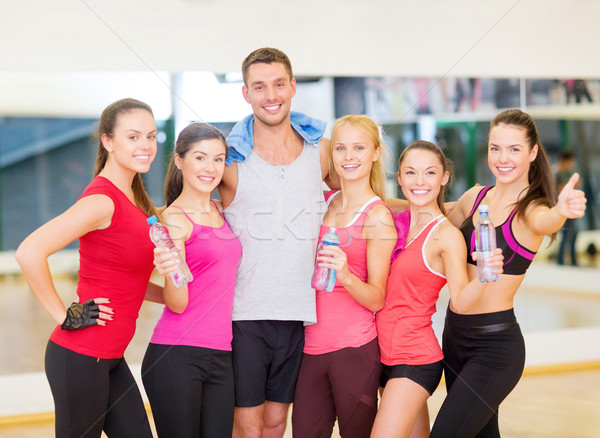 group of happy people in gym with water bottles Stock photo © dolgachov