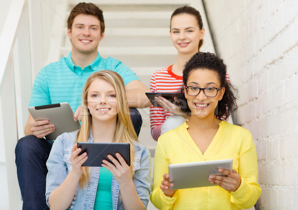 smiling students with tablet pc computer Stock photo © dolgachov