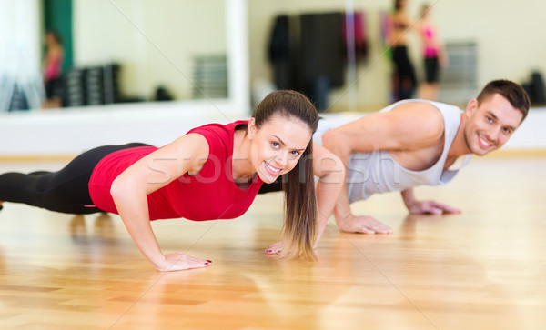 Stock photo: smiling couple doing push-ups in the gym