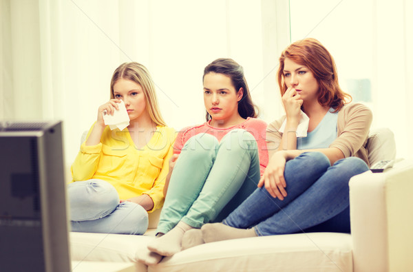 three sad teenage girl watching tv at home Stock photo © dolgachov