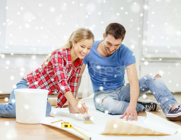 Stock photo: smiling couple smearing wallpaper with glue