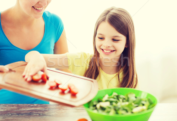 little girl with mother adding tomatoes to salad Stock photo © dolgachov