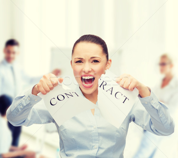 Stock photo: serious businesswoman tearing contract