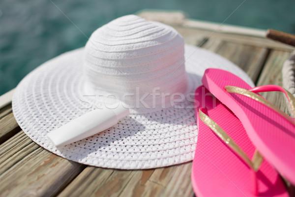 Közelkép kalap napozókrém házi cipők vízpart tengerpart Stock fotó © dolgachov