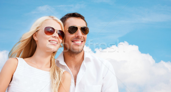 happy couple in shades over blue sky background Stock photo © dolgachov