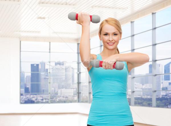 Glimlachende vrouw biceps gymnasium fitness sport Stockfoto © dolgachov