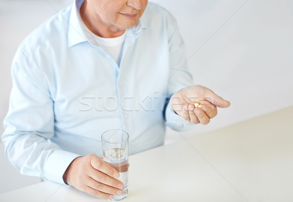 close up of old man with pills and water glass Stock photo © dolgachov