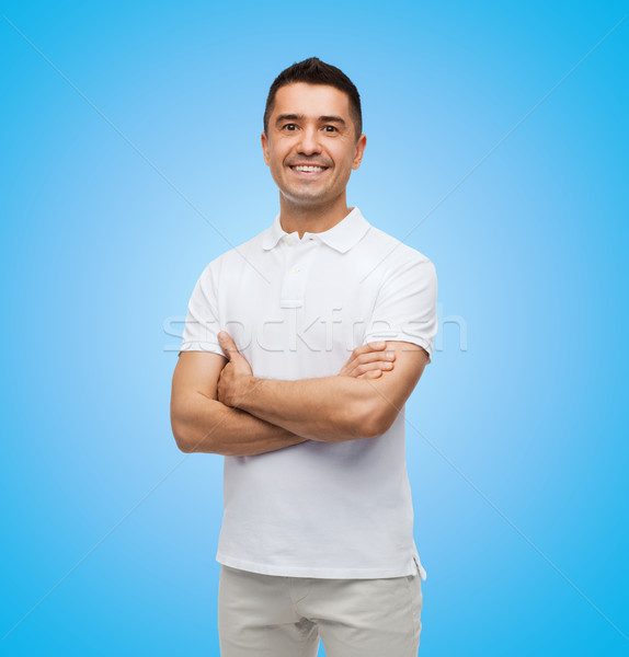 smiling man in white t-shirt with crossed arms Stock photo © dolgachov