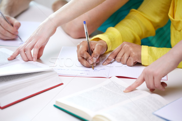 close up of students hands writing to notebooks Stock photo © dolgachov