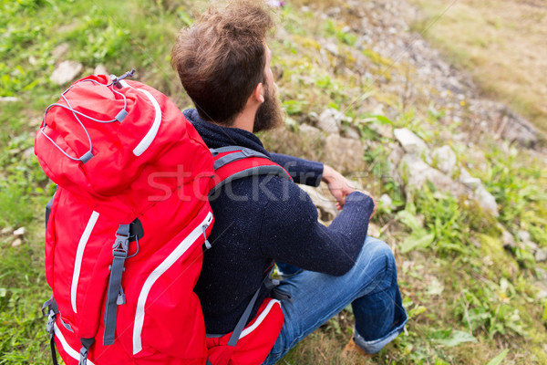 man hiker with red backpack sitting on ground Stock photo © dolgachov