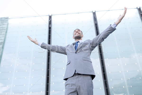 young smiling businessman over office building Stock photo © dolgachov