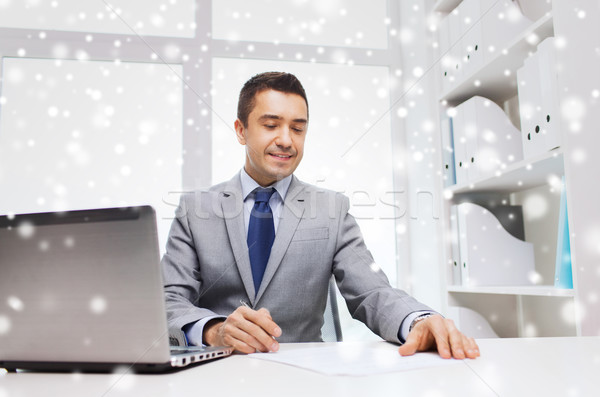 Stock photo: smiling businessman with laptop and papers
