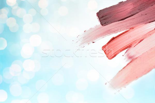 close up of lipstick smear sample over blue lights Stock photo © dolgachov