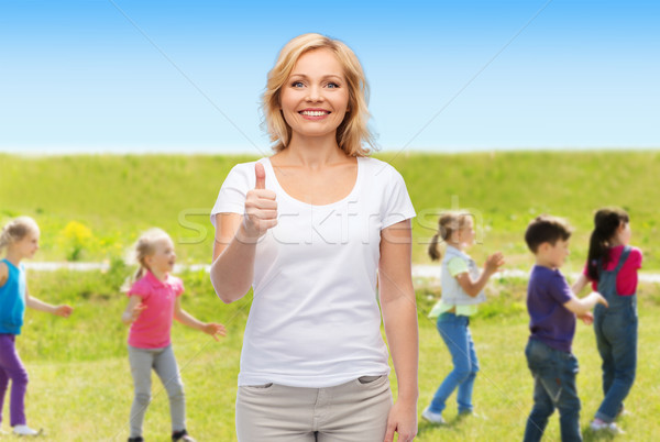 woman showing thumbs up over group of little kids Stock photo © dolgachov