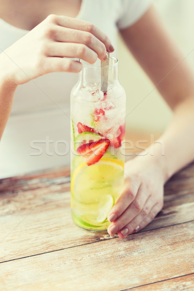 close up of woman with fruit water in glass bottle Stock photo © dolgachov