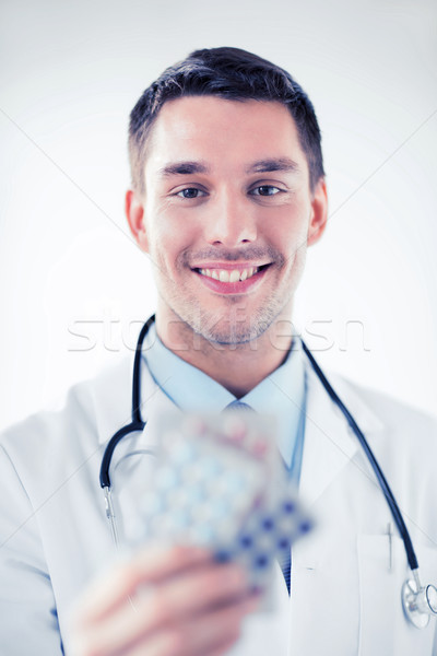 young male doctor with packs of pills Stock photo © dolgachov
