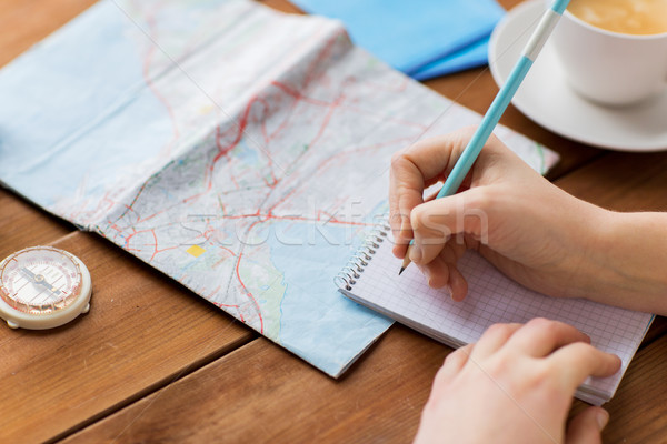 Stock photo: close up of traveler hands with notepad and pencil