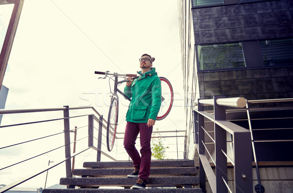 young hipster man carrying fixed gear bike in city Stock photo © dolgachov