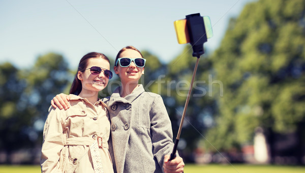 happy girls with smartphone selfie stick in park Stock photo © dolgachov