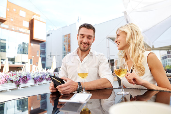 happy couple with wallet paying bill at restaurant Stock photo © dolgachov
