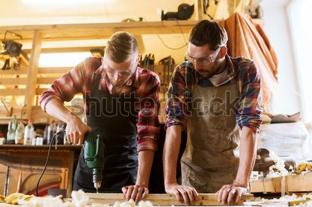 carpenters with ruler and wood plank at workshop Stock photo © dolgachov