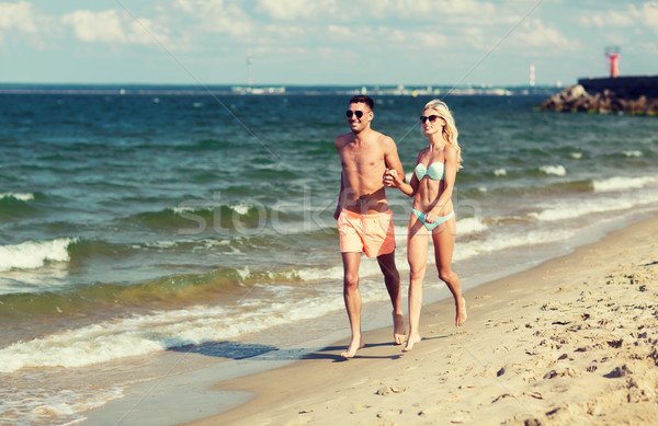 happy couple in swimwear running on summer beach Stock photo © dolgachov