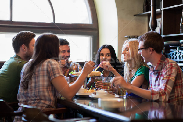 happy friends with beer eating at bar or pub Stock photo © dolgachov