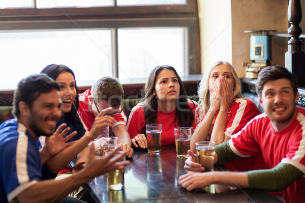 fans or friends watching football at sport bar Stock photo © dolgachov