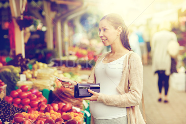 pregnant woman with wallet buying food at market Stock photo © dolgachov
