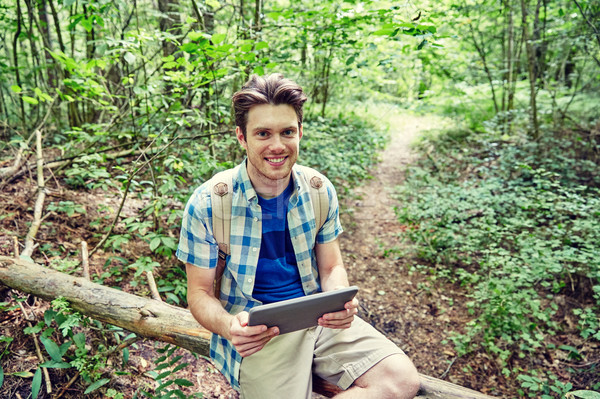 happy man with backpack and tablet pc in woods Stock photo © dolgachov