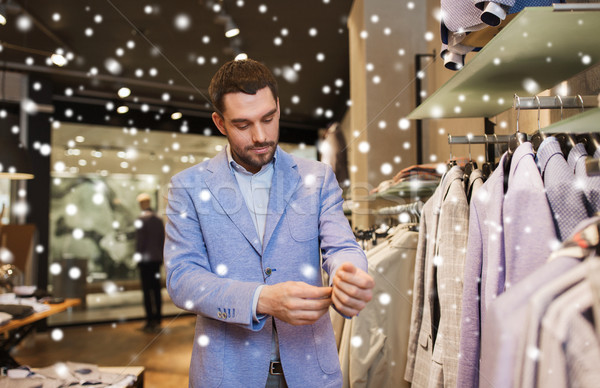 happy young man trying jacket on in clothing store Stock photo © dolgachov