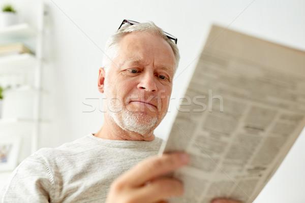 close up of senior man reading newspaper at home Stock photo © dolgachov