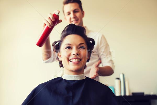 happy woman with stylist making hairdo at salon Stock photo © dolgachov