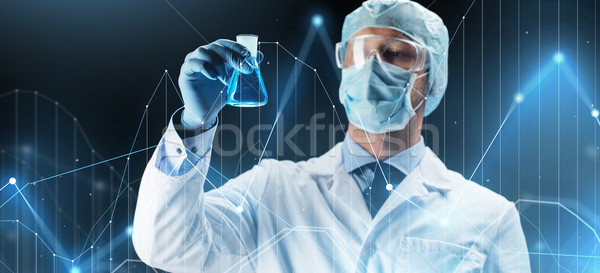 scientist in mask holding flask with chemical Stock photo © dolgachov