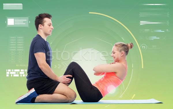 happy sportive man and woman doing sit-ups Stock photo © dolgachov
