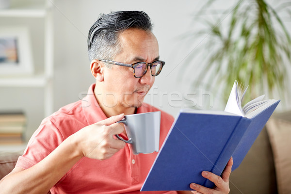 man sitting on sofa and reading book at home Stock photo © dolgachov
