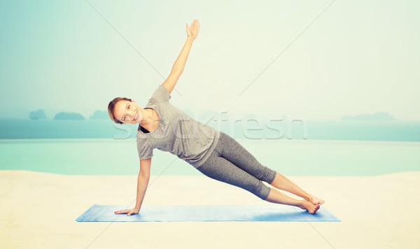 woman making yoga in side plank pose on mat Stock photo © dolgachov