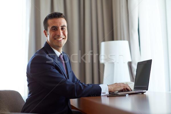 Empresário datilografia laptop quarto de hotel pessoas de negócios tecnologia Foto stock © dolgachov