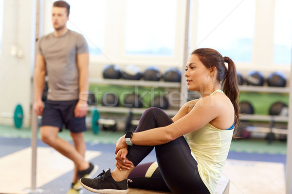 man and woman with heart rate tracker in gym Stock photo © dolgachov