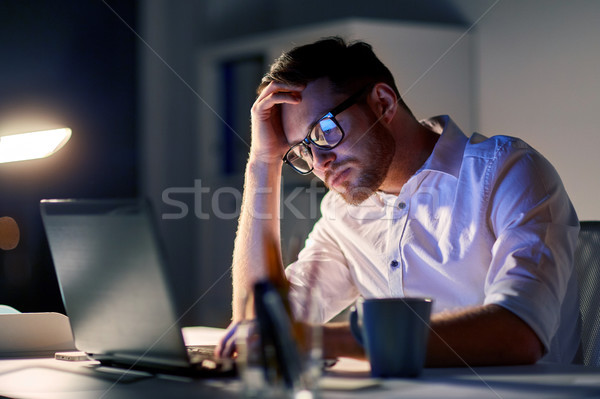 businessman with laptop thinking at night office Stock photo © dolgachov